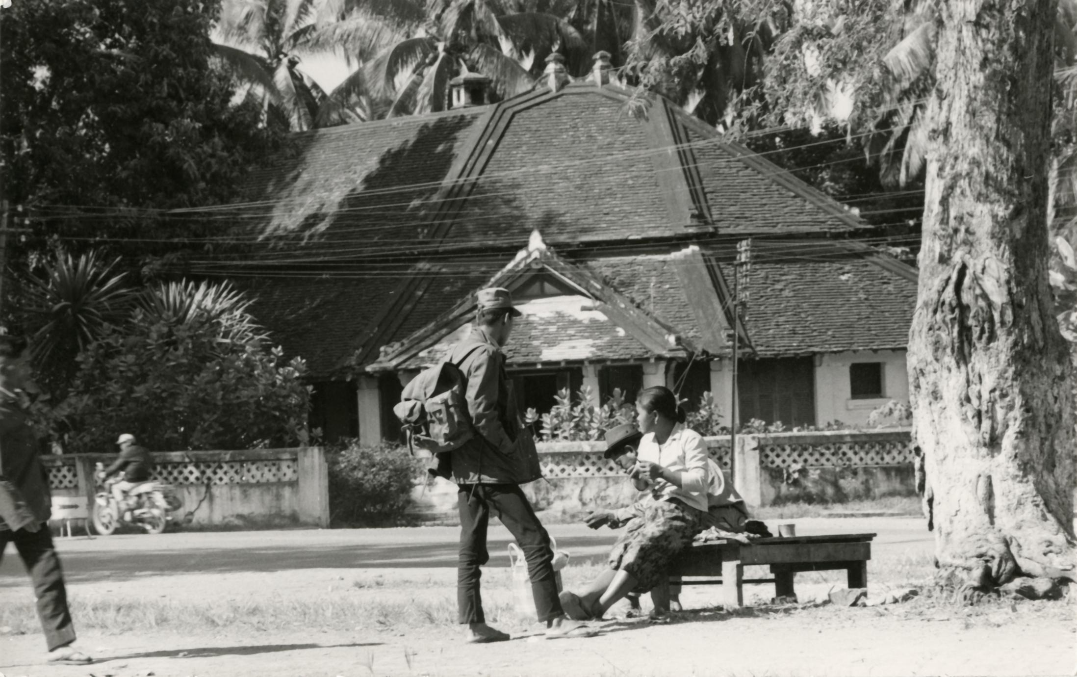 A soldier stands and talks with his wife in the city of Luang Prabang in Luang Prabang Province
