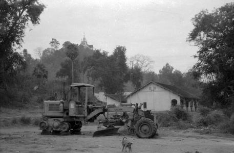 Large modern road grader at work, Phu Si monument on hill in background