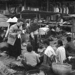 Western woman buying vegetables from women (missionary)