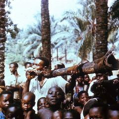 Man Playing Tree Root Trumpet in Crowd