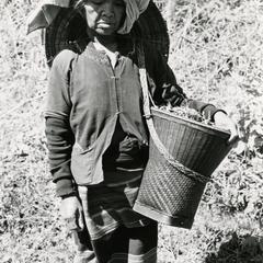 A Nyaheun woman walks along a road carrying a basket full of food in Attapu Province