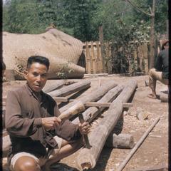 Man making house posts