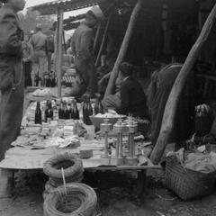 Man selling kerosene lanterns, coils of wire, and notions, soldier on left