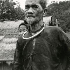 An elderly Blue Hmong (Hmong Njua) man stands in a Hmong village in the vicinity of Muang Vang Vieng in Vientiane Province