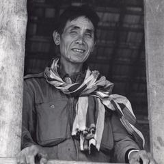 Laven villager in Houei Kong Cluster looking out from his house window in Attapu Province
