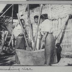 Three Filipinos pounding rice