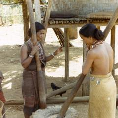 Two Nyaheun women are pounding rice in a village in Attapu Province