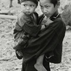 Akha boy holds baby brother in the Akha village of Phate in Houa Khong Province