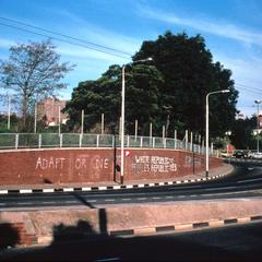 """Prime Minister P.W. Botha's Slogan, """"Adapt or Die,"""" Painted on Wall Facing Jan Smuts Avenue, Johannesburg, During Anti-Republic Day Activities"""