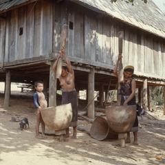 Khmu' women and child dehusking rice