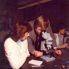Instructor and student looking through microscopes