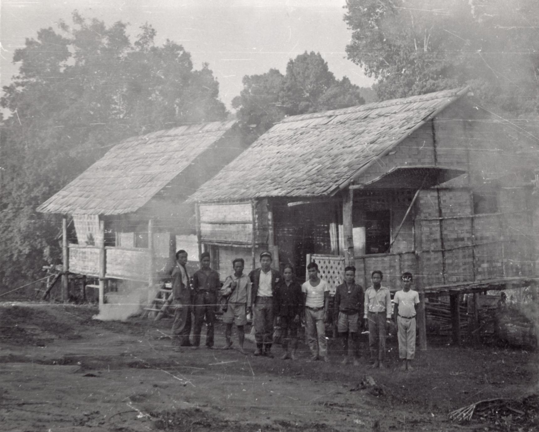 Nine village men stand in front of two houses in Houei Kong Cluster in Attapu Province