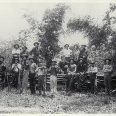 U.S. soldiers, some with musical instruments, pose for the camera in a field, 1899