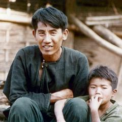 A Yao (Iu Mien) father and son are seated outside their house in Houa Khong Province