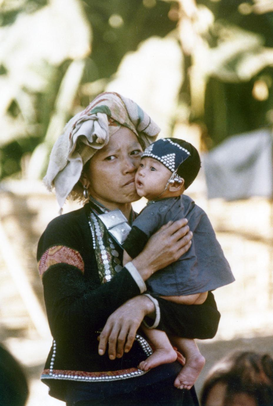 A Yellow Lahu (Lahu Shi) mother holds her infant in Houa Khong Province