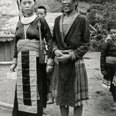 A White Hmong and a Blue Hmong (Hmong Njua) woman stand in a Hmong village in the vicinity of Muang Vang Vieng in Vientiane Province