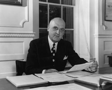 Fred, Edwin Broun seated at his desk