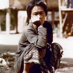 A Khmu' woman is squatting in her village in Houa Khong Province