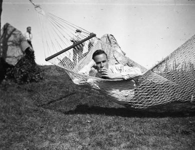 Young man smoking in hammock