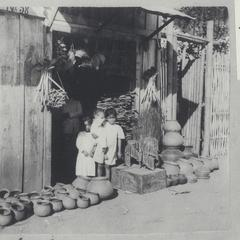 Three Filipino children standing in front of store among pots