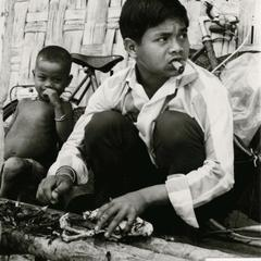 A Nyaheun boy plucks a chicken on his porch in Attapu Province