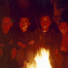 Four White Hmong boys sitting around a campfire in Houa Khong Province