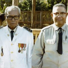 Two former district chiefs pose for a photograph in Attapu Province