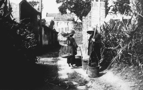 [Two women carrying materials]