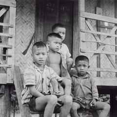 Four Laven boys are seated on the steps of a village house in Houei Kong Cluster in Attapu Province