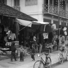 View of a number of shops along main street, bicycles lined up, selling tin pails, clothing, electric pole visible, upper story probably used for residence
