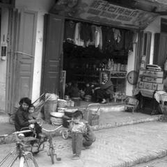 View of three shops, children of merchants playing on streets, with tri-cycle and child's stroller visible on right, woman and child in left foreground, central shop has trilingual sign