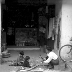 Young woman with merchant's children playing outside shop; galvanized tin pails on left