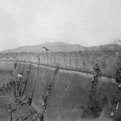 Chinese troops scale a fortress wall.
