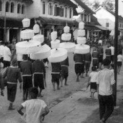 Officials and Kammu (Khmu') ceremonial guards, some carrying multi-tiered parasols, making their way through the business district prior to assembly, children watching the action