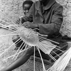 Man Weaving Basket with His Daughter Looking On