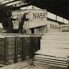 Boxed Nash automobiles are loaded onto railroad cars