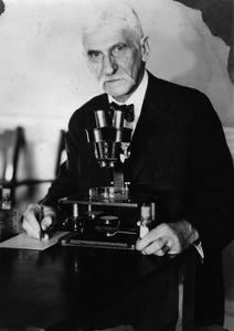 Birge, Edward A. with microscope