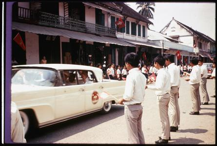 Crown prince traveling to pagoda, Vientiane, greeted by school children with Lao flags