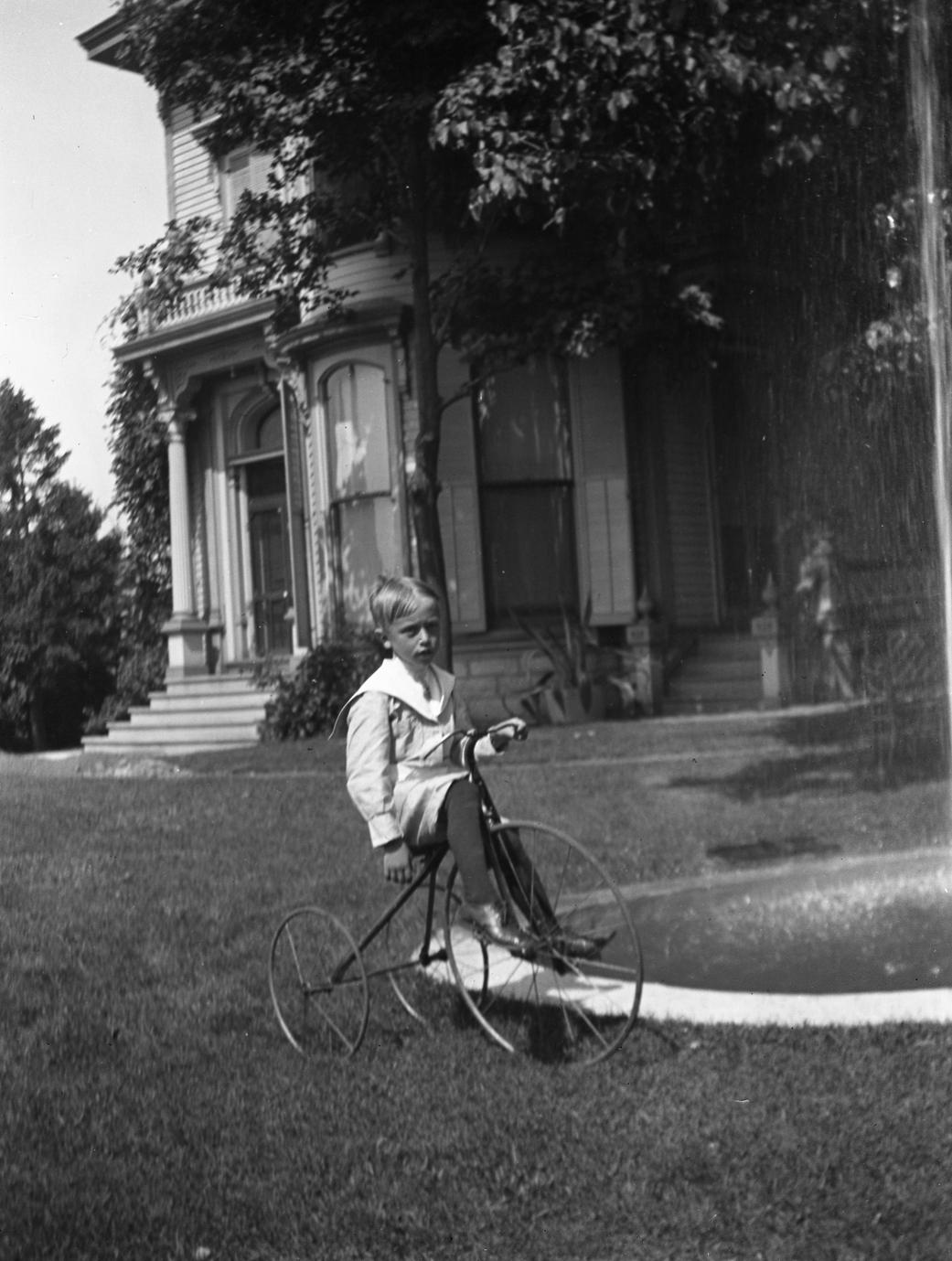 Frederic Leopold riding tricycle in front of Burlington house