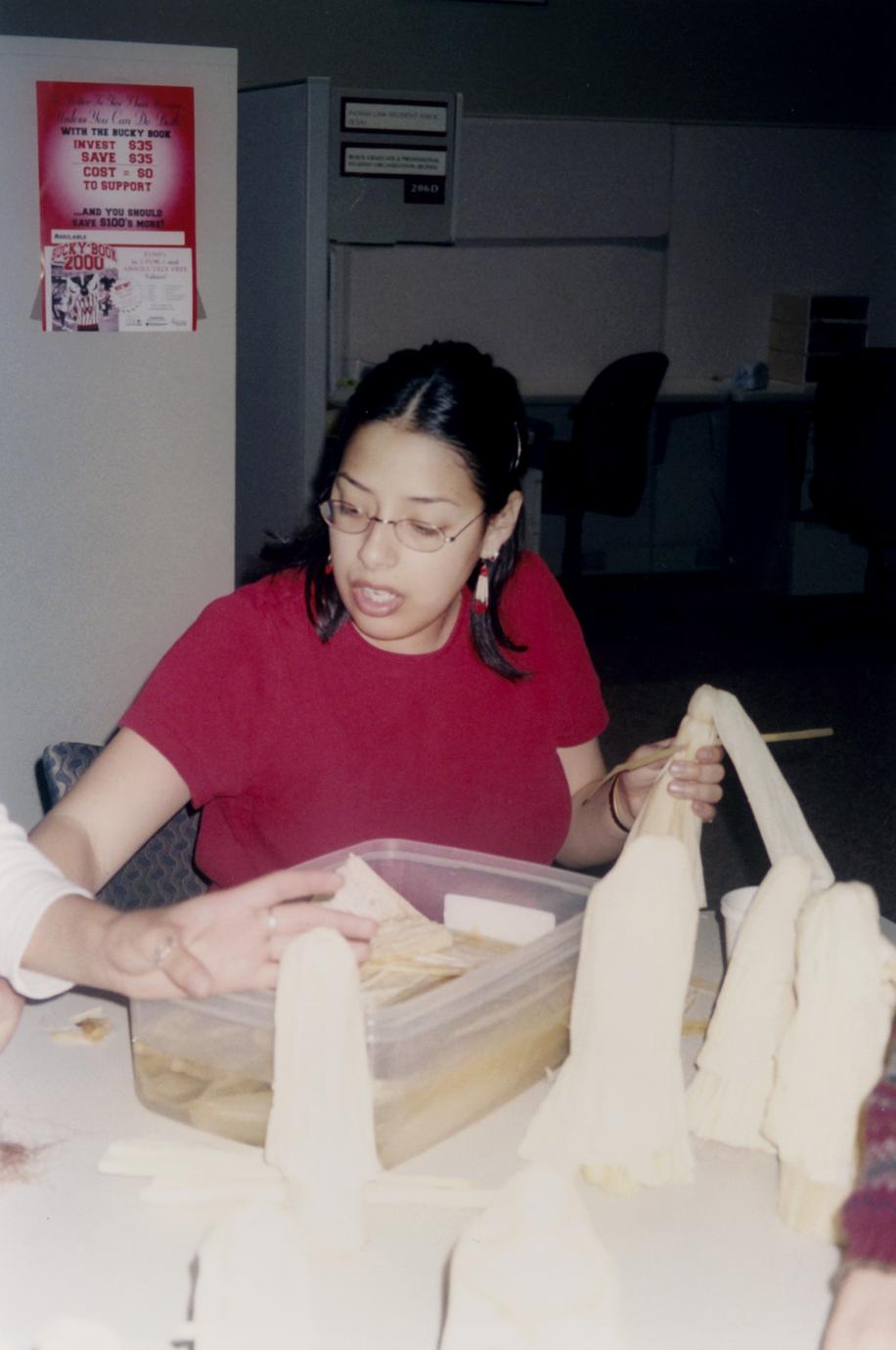 Female student making cornhusk dolls