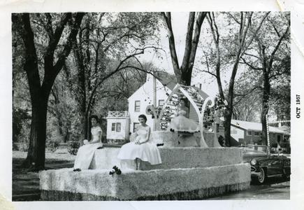Sigma Tau Gamma - 3 female students riding on Homecoming float in the Homecoming parade