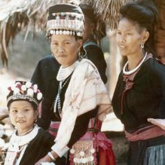 Two Hmong women and girl stand near a house in Houa Khong Province
