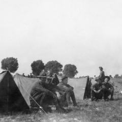 Soldiers of the US Army's 15th Infantry Regiment squatting in front of their tents.