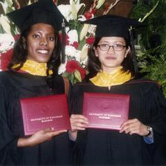 Two graduates and diplomas at 2002 graduation