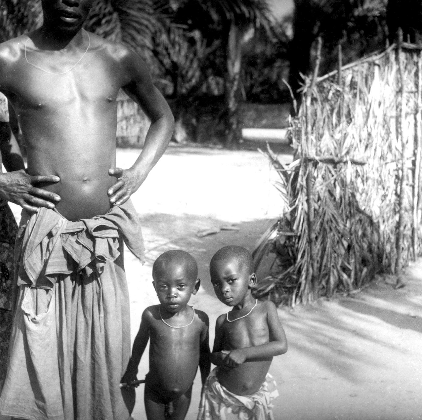 Two Young Kuba-Bieng Children Posing with Their Father Outside Their Compound