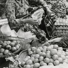 A woman sells oranges and eggs in the Pakxe morning market in Sedone Province