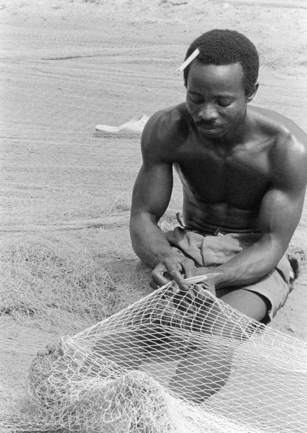 Man Mending Net for Ocean Fishing