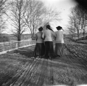 Three women walking down road