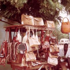 Vendor in Bolgatanga Displays Leather Handbags for Sale