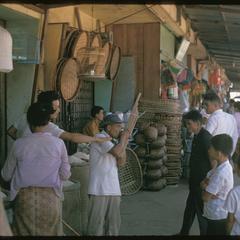 Morning Market : man playing khene near basket stores